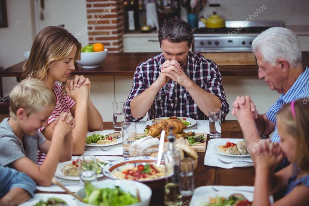 family praying around table - 1023×682