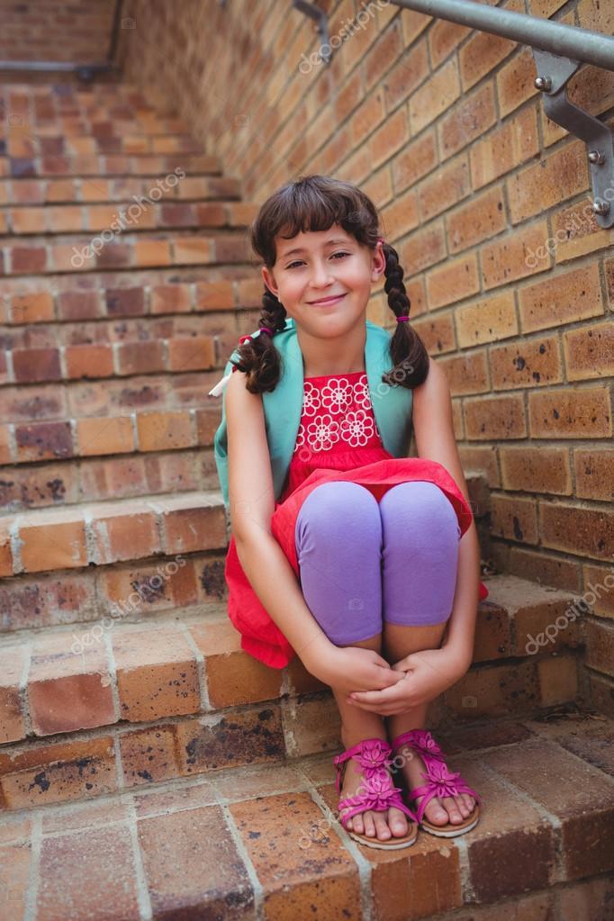 d7739aee3 Colegiala sonriente sentada en las escaleras — Fotos de Stock ...