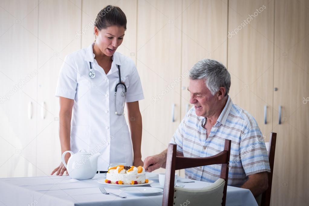 Female Doctor Celebration Seniors Man Birthday In Living Room At Home Photo By Wavebreakmedia