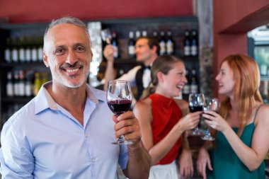 smiling man holding glass of wine