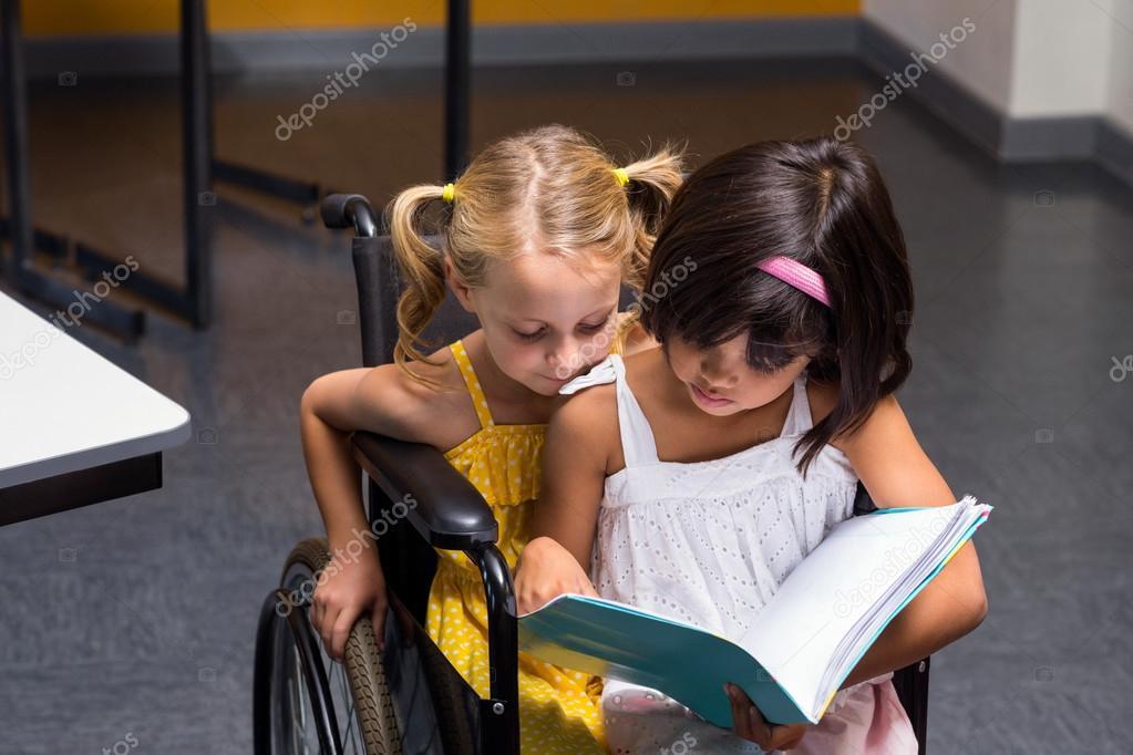 Sedie A Rotelle Leggere : Ragazze che si siedono sulla sedia a rotelle leggere libro u foto