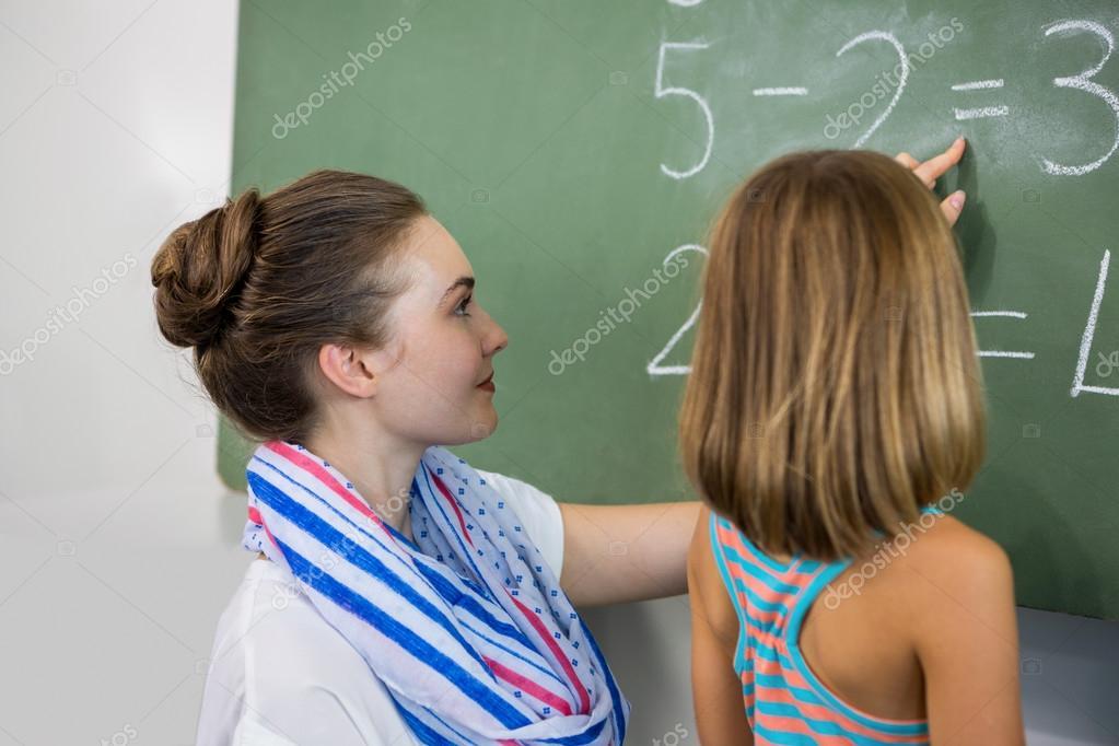 teacher teaching girl on chalkboard stock photo wavebreakmedia