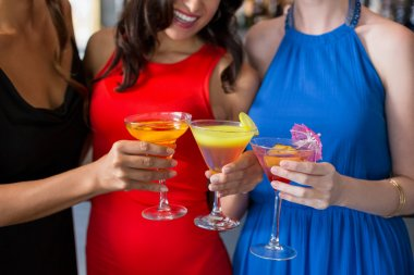 Happy female friends holding glass of cocktail