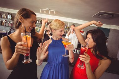 Female friends holding glass of cocktail while dancing