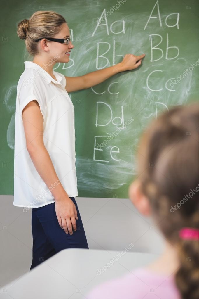 smiling teacher teaching kids on chalkboard in classroom stock