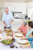 Starší muž podávající jídlo do rodiny