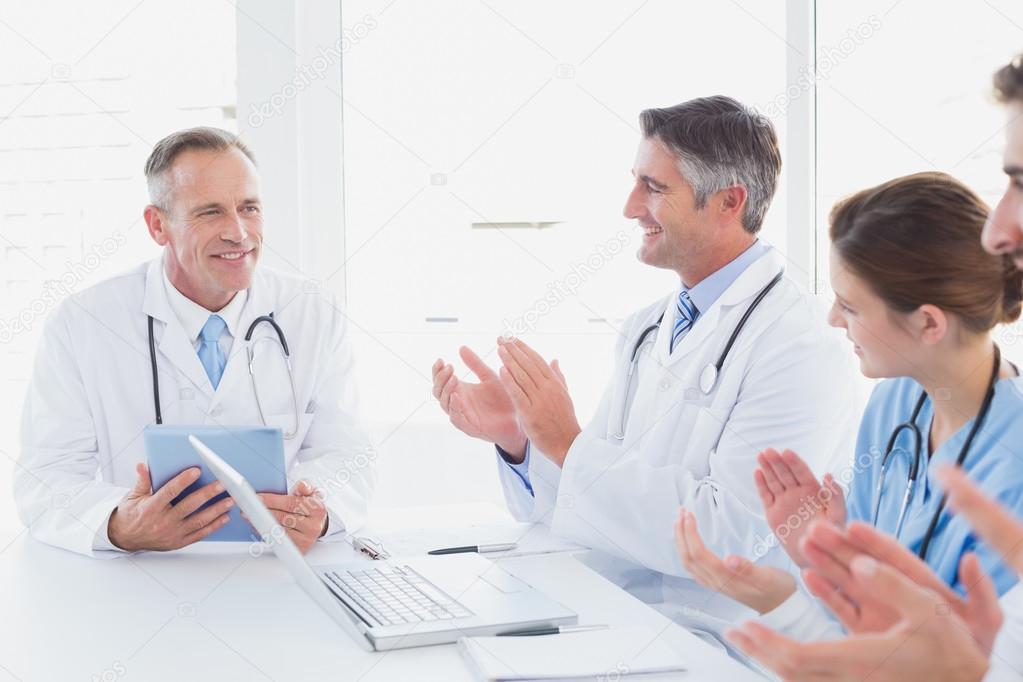 doctores aplaudiendo un compañero médico — fotos de stock