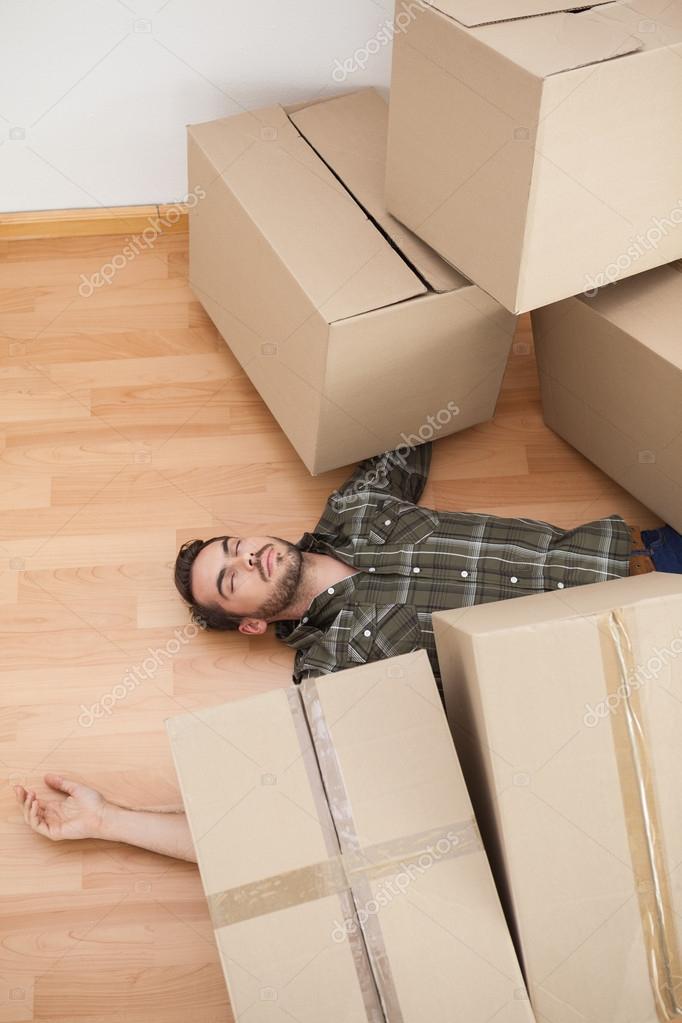 Mann, Liegend Unter Gefallenen Kisten Zu Hause Im Wohnzimmer U2014 Foto Von  Wavebreakmedia