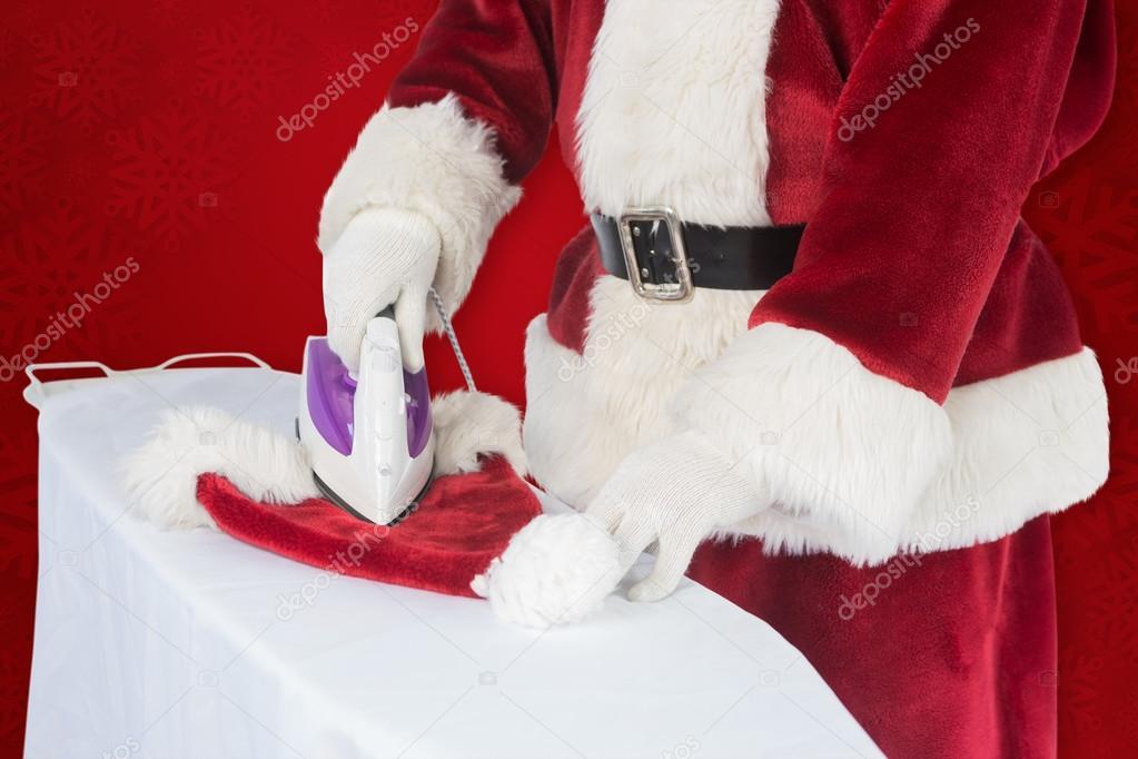 897c64dec2f30 Papá Noel es planchar su sombrero — Foto de stock © Wavebreakmedia ...