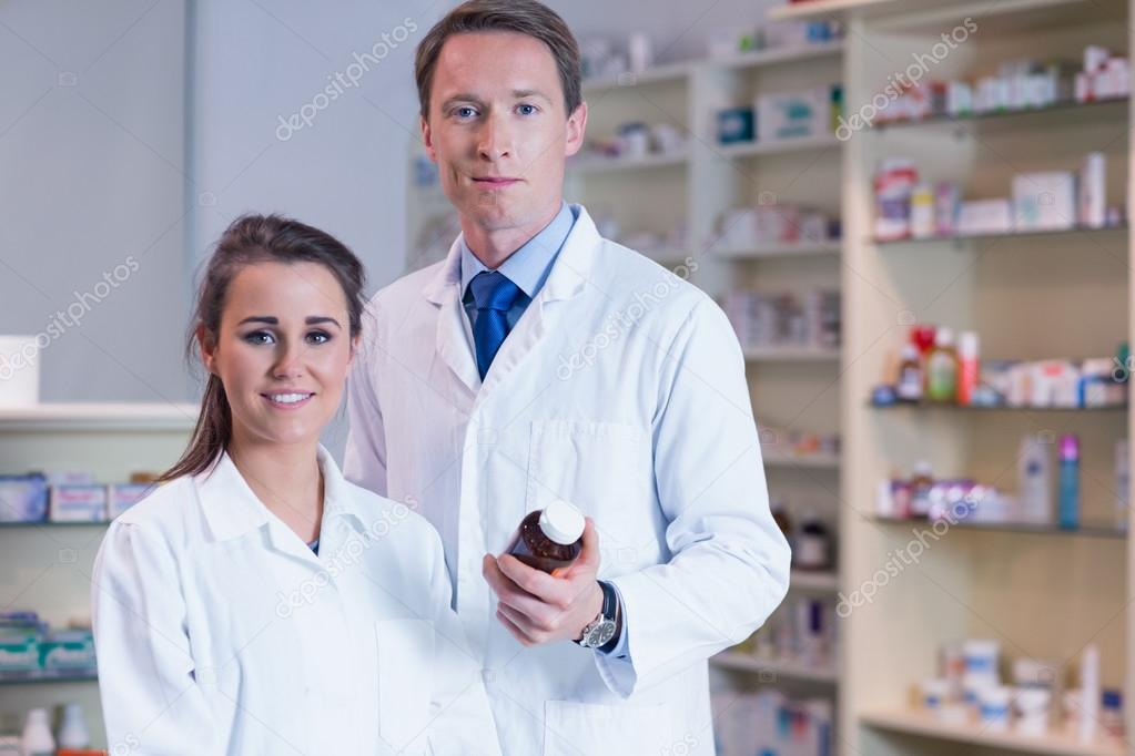 Pharmacist showing medication to his trainee — Stock Photo ...