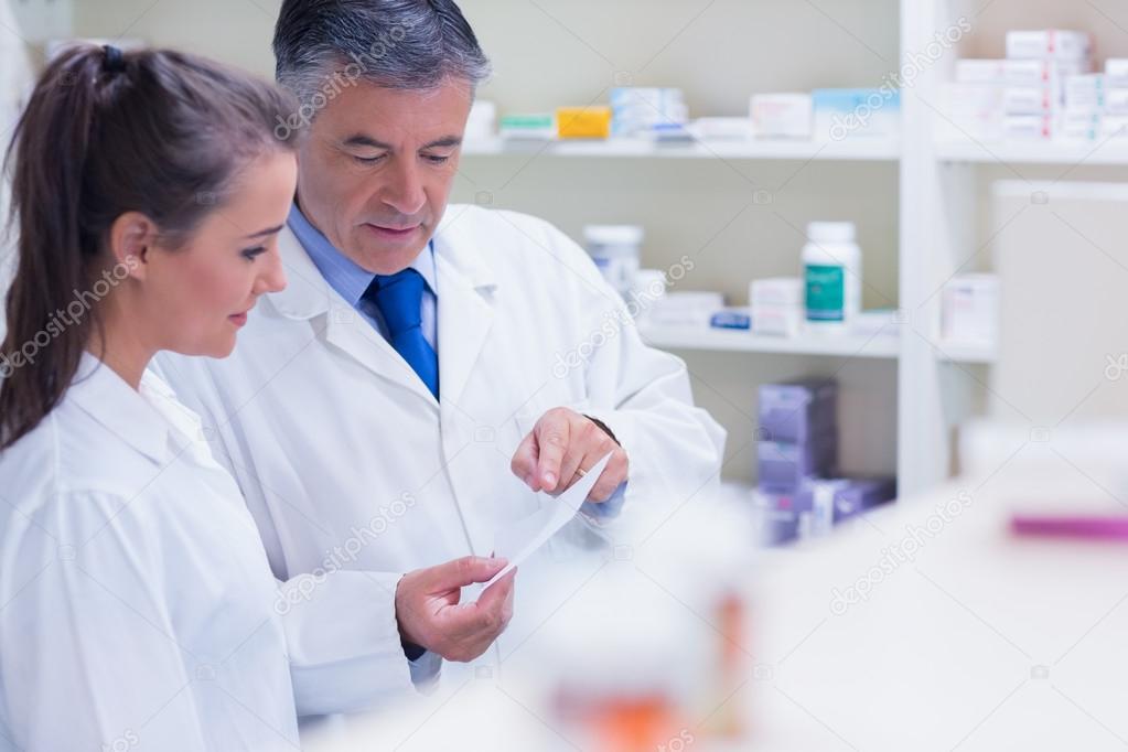 Pharmacist explaining a prescription to his trainee — Stock Photo ...