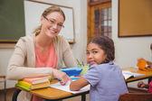 Pěkná učitelka pomáhá žák ve třídě