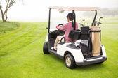 Golfista jízdy v jeho golfového kočárku
