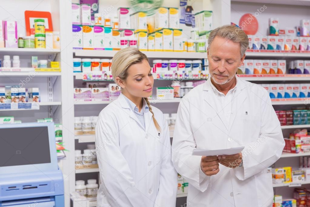 Pharmacist and trainee talking together about prescription — Stock ...