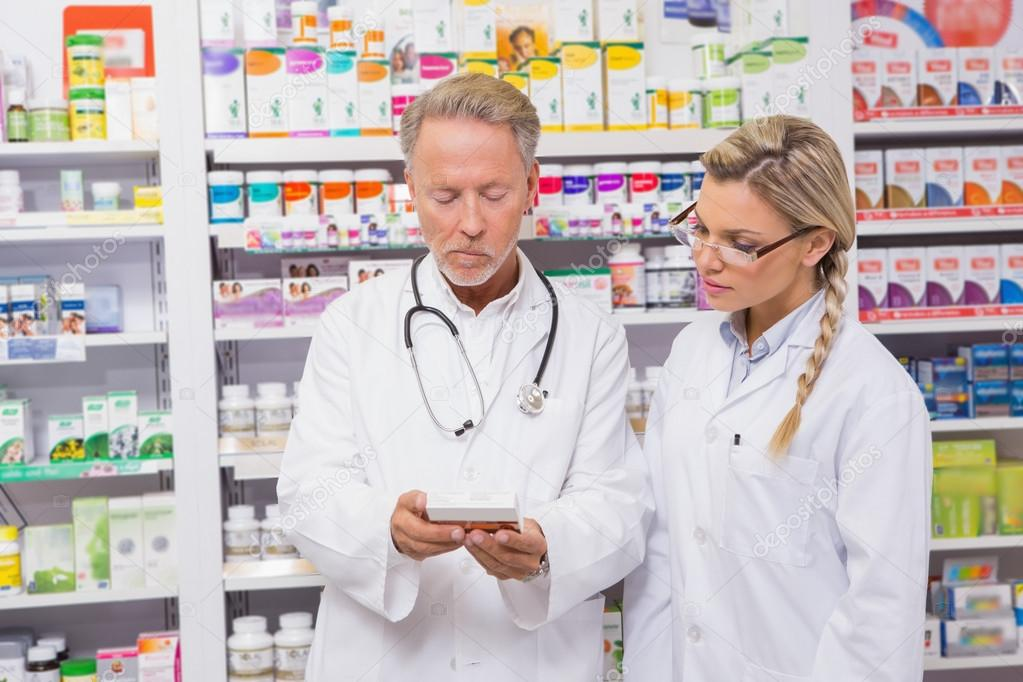 Pharmacist speaking with his trainee about medicine — Stock Photo ...