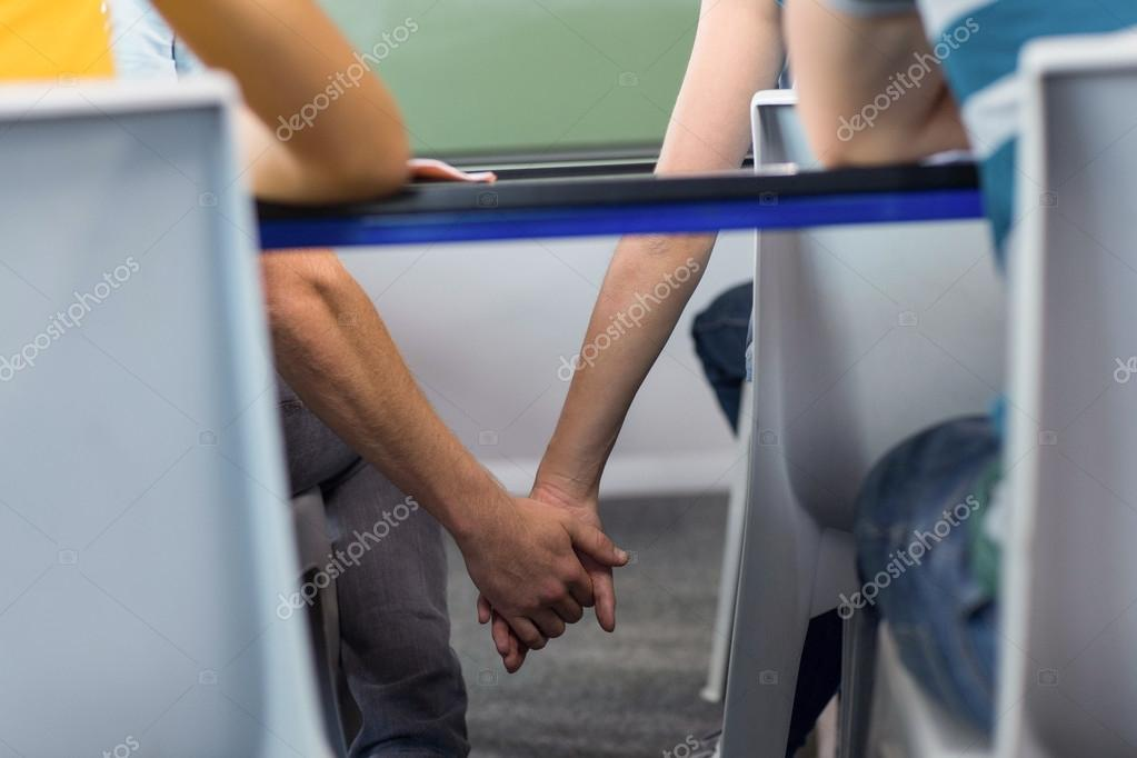 Couple main dans la main sous le bureau en salle de classe