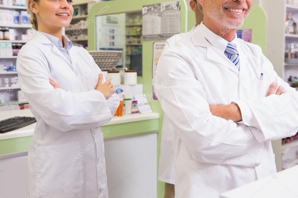 Smiling pharmacist and his trainee with arms crossed — Stock Photo ...