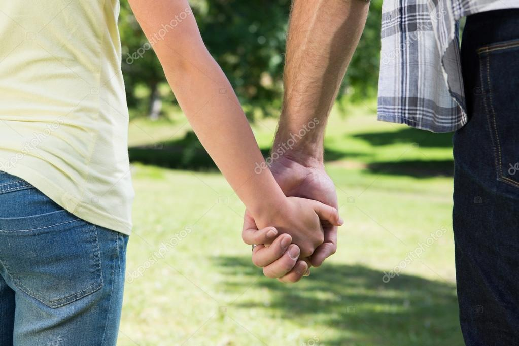 Father And Daughter Holding Hands In The Park Stock Photo