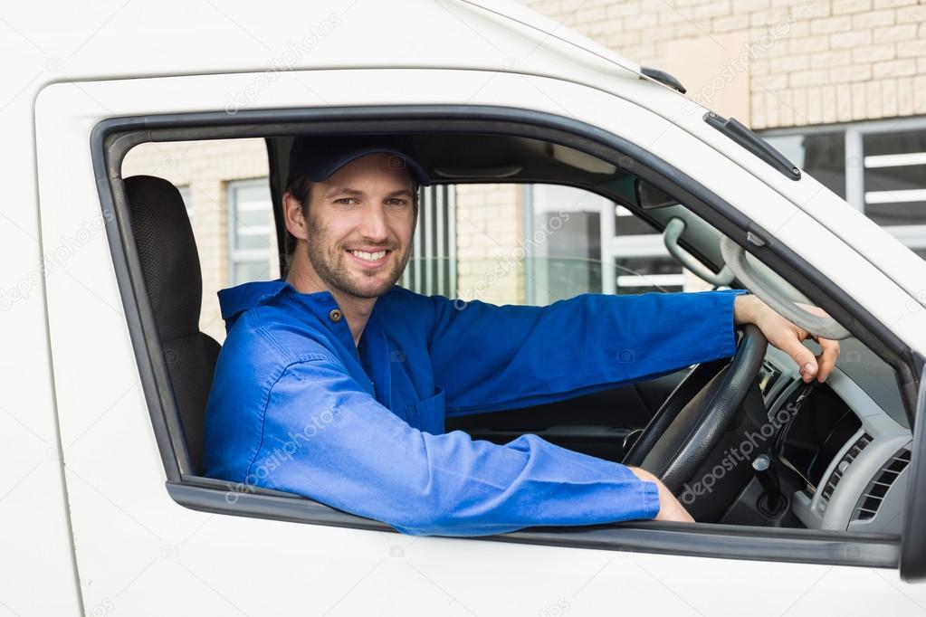 Delivery driver smiling at camera in his van — Stock Photo ...