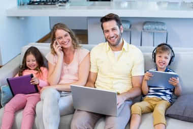 Happy family on the couch together using devices