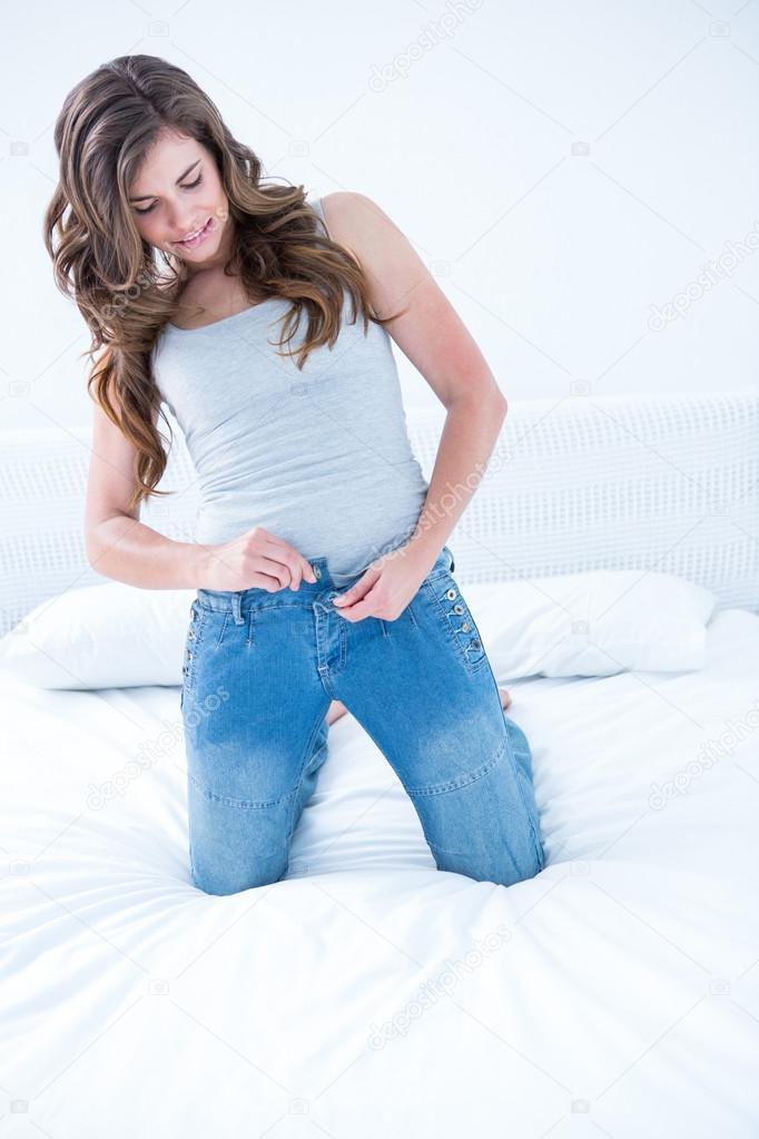 Attraktive Frau Setzen Auf Enge Jeans Stockfoto Wavebreakmedia