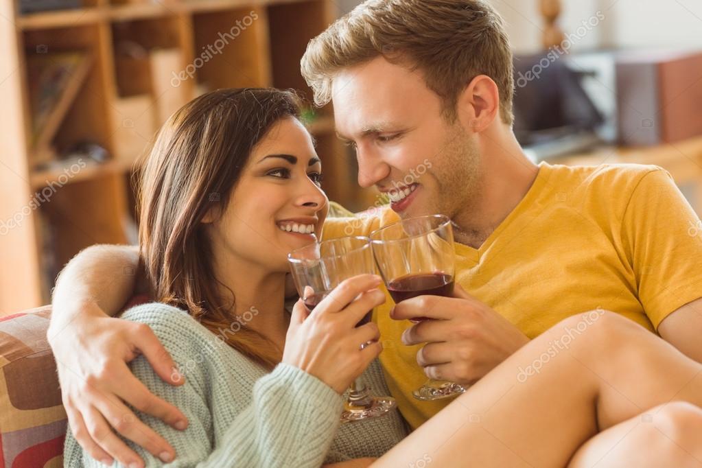 Paar kuschelt auf Couch mit Rotwein - Stockfotografie