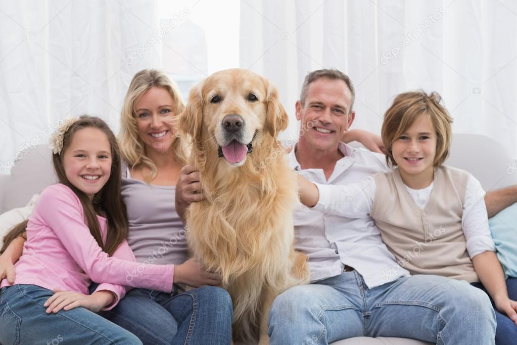 Family Petting Golden Retriever On The Couch Stock Photo
