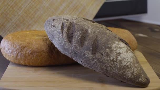 fekete kenyér fekszik egy vágódeszkán, egy vekni fehér kenyérrel együtt..