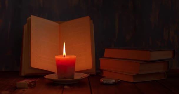 zátiší, svíčka hoří na stole, vedle ní je otevřená kniha a hodiny, retro