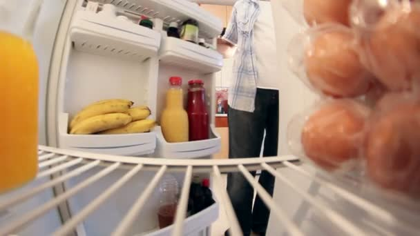 Man looks in the fridge to get orange juice