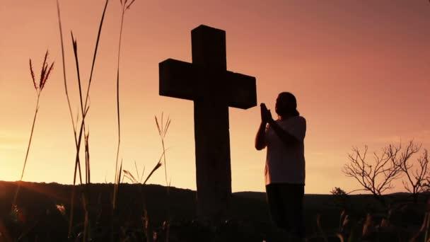 člověk se modlí pod kříž