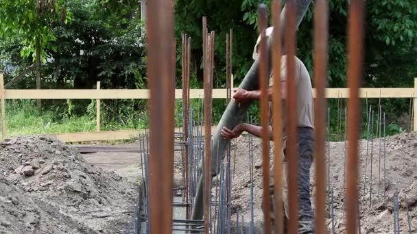 Stavební dělník vylévající cement a beton čerpadlo trubice