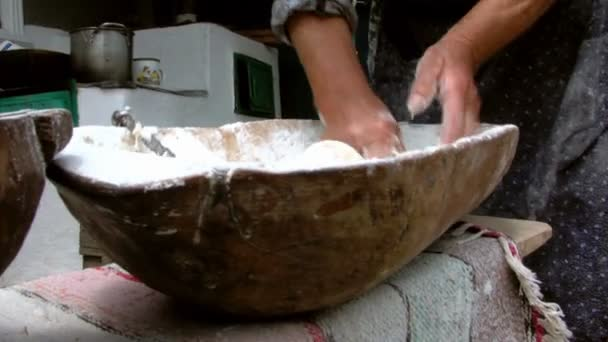 Old woman kneading dough in a wooden bowl