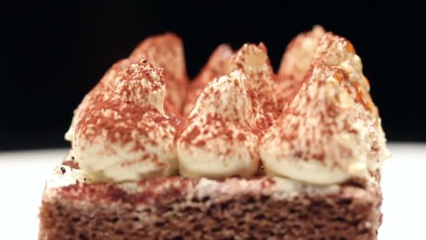 Zblízka tiramisu dort na bílém štítku, otáčení