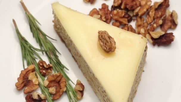 Zblízka na ořechový dort s vanilkovým fondán na bílém štítku, otáčení