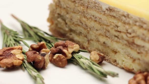 Közelről egy dió tortát a vanília fondant fehér tányérra, forgatható