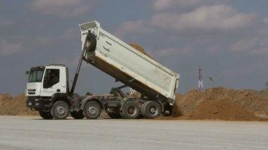 Dumper Truck Unloading Soil At Construction Site During Road Works