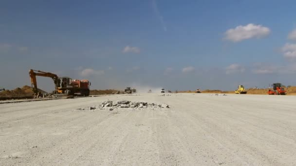 Heavy construction equipment working on an airport runway, time lapse