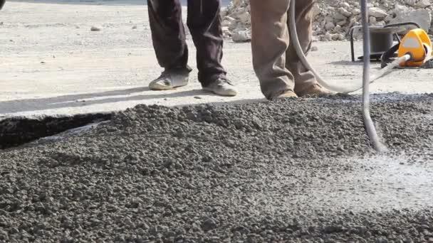 Építőipari munkások tömörítés folyékony cement-ba egy kifutópálya építése