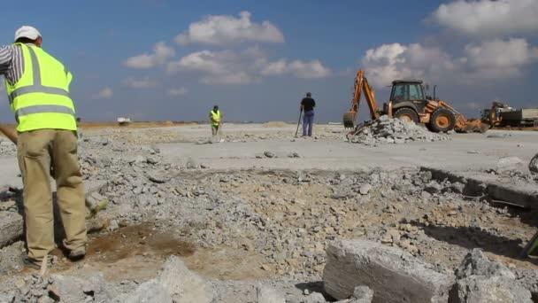 Egy kifutópálya építkezésen a shoveling munkavállalók