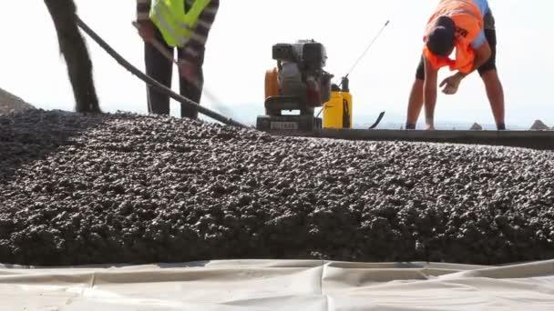 Stavební dělníci komprimování tekutých cementu do stavby dráhy