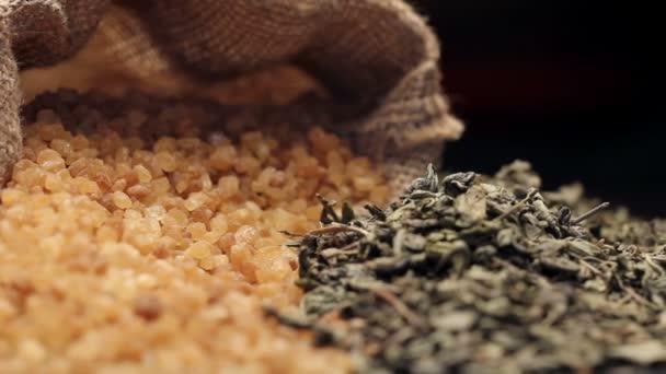 Barna cukor juta zsák és egy halom szárított zöld tea levelek, forgatható