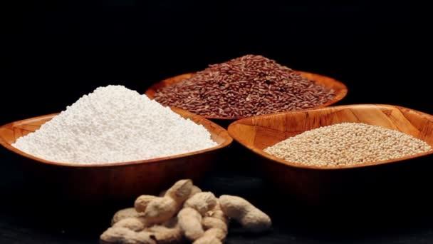 Červená rýže, proso zrna, tapioca perly v malých miskách a hromadu arašídů, rotační