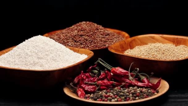 Červená rýže, proso zrna, tapioca perly v malých miskách a hromadu sušených chilli, rotační