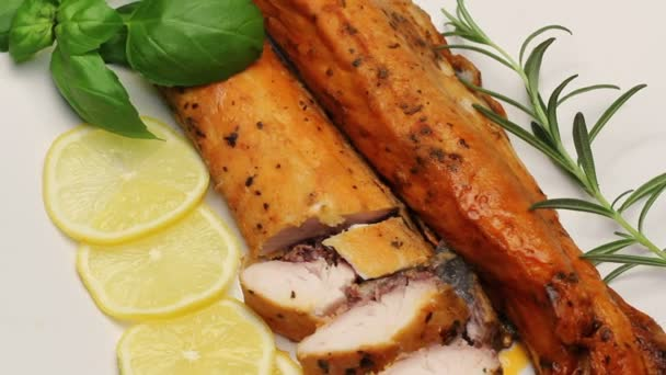 Smoked carp with aromatic herbs and lemon on white plate, rotating