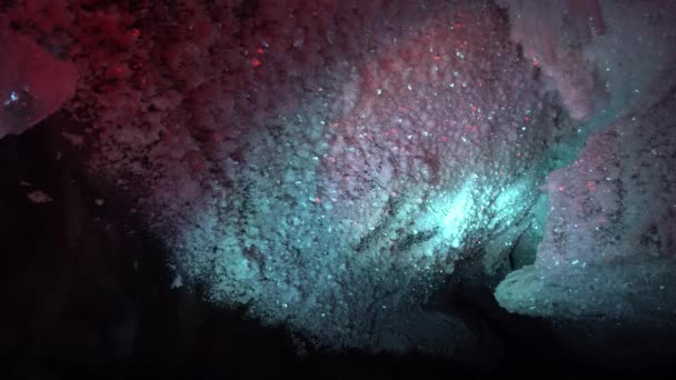 In an ice cave with colored lighting from lanterns