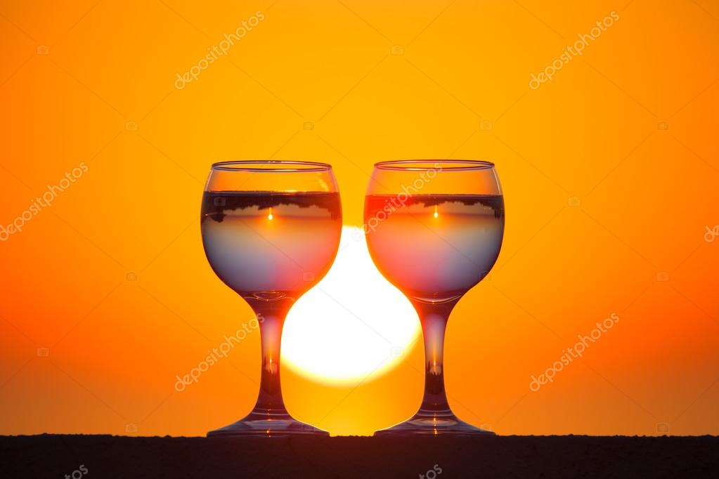 Glasses of white vine with reflections of houses and view to bea