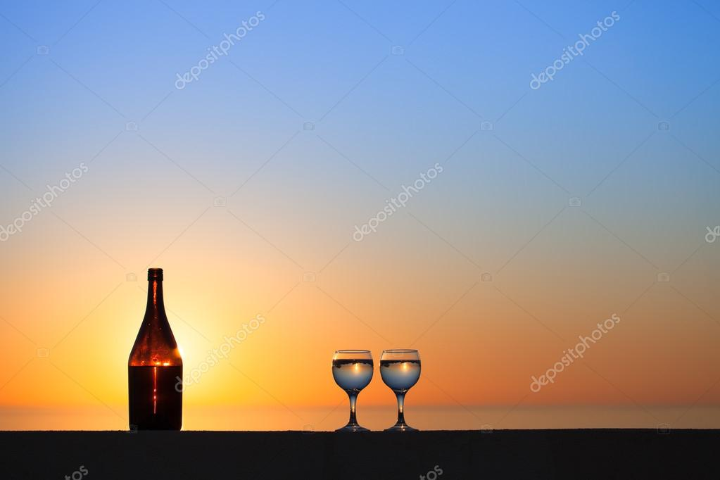 Bottle and glasses of white vine with reflections of houses and
