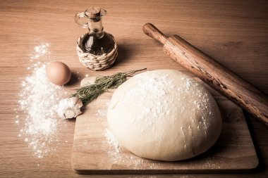 dough on a board with flour. olive oil, eggs, rolling pin, garli