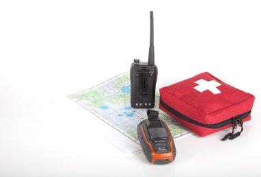 Map, gps navigator, portable radio and first aid kit on a light